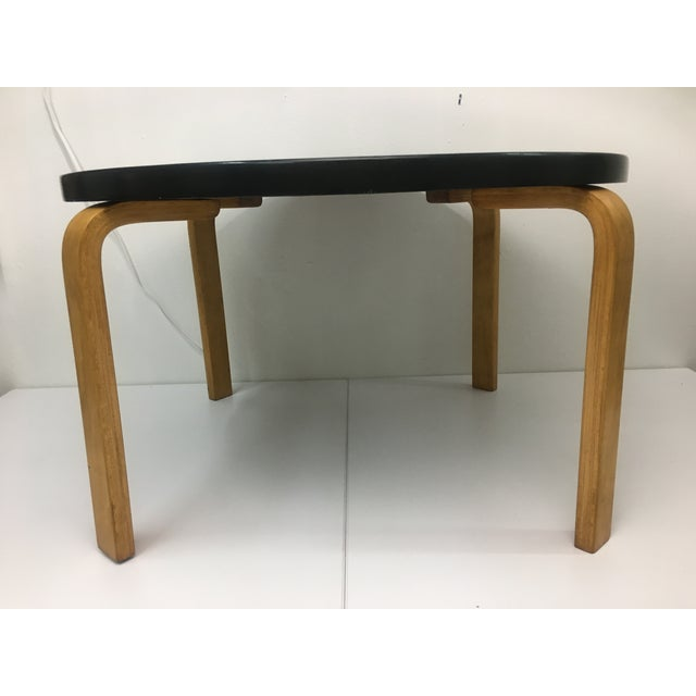 The top of the table is a nicely grained birch in an ebonized finish; the legs are the same birch in the natural wood...