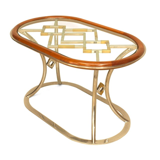 Pair of French post-war design (1970s) oval coffee tables with a mahogany rim holding a glass top over an open brass...
