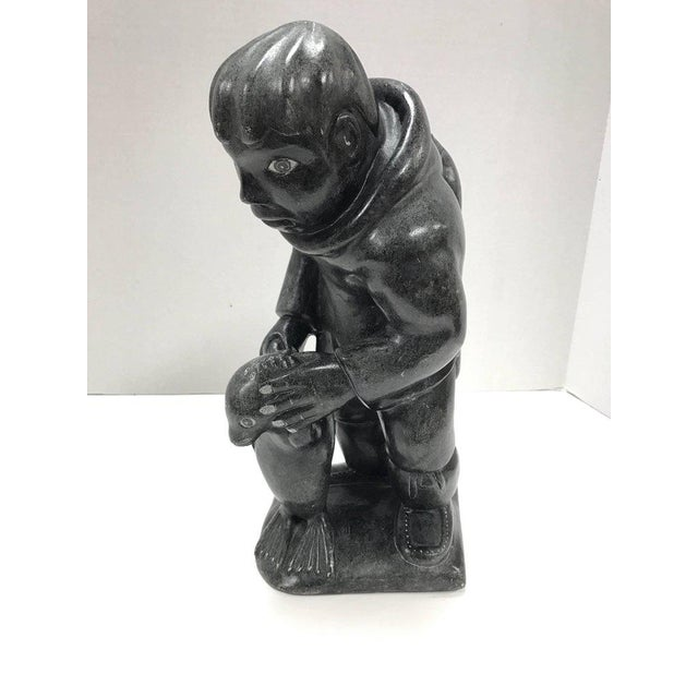Inuit heavy soapstone sculpture showing Eskimo hunter with prey. Hallmarked at bottom of base with tag that reads...