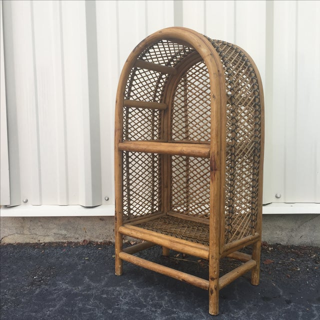 This vintage shelf features a weaved back and durable rattan frame offering two shelves for opened storage.
