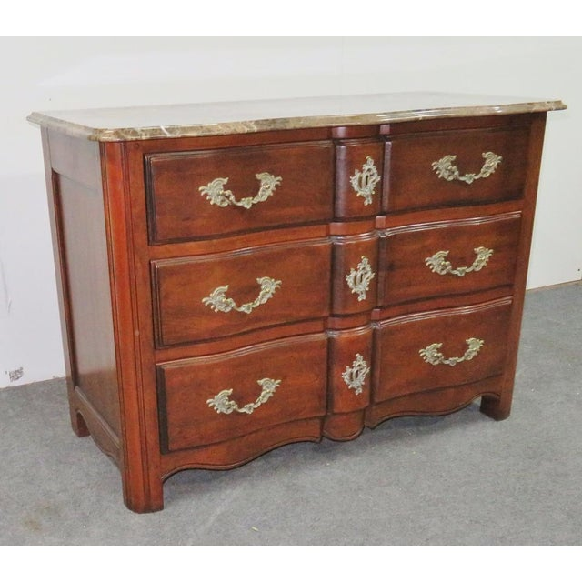 Beige marble top with beveled edge. Cherry with decorative metal hardware.