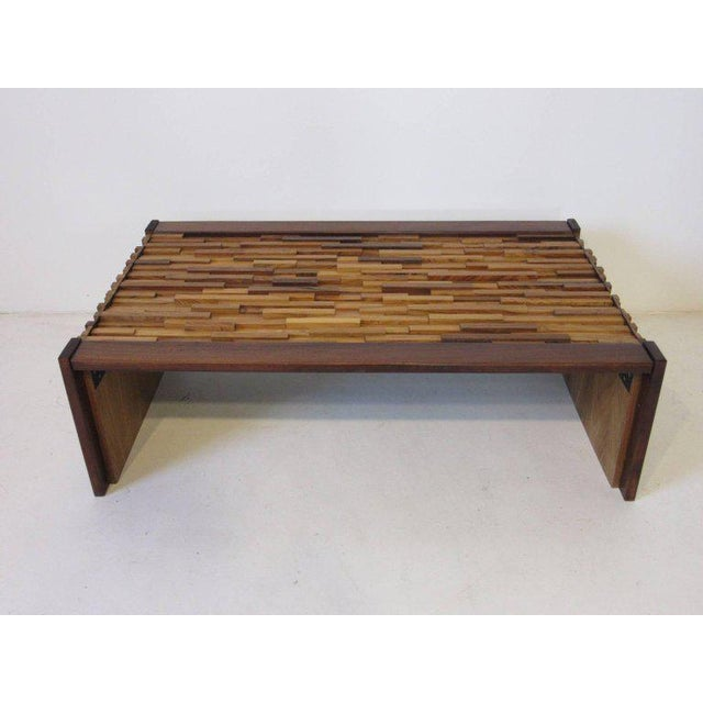 A well constructed rich textured coffee table with form fitted pieces of rosewood topped with glass, also made with...
