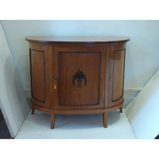 20th Century satinwood demi-lune buffet with three cabinet doors, the locks in working order, interior adjustable...