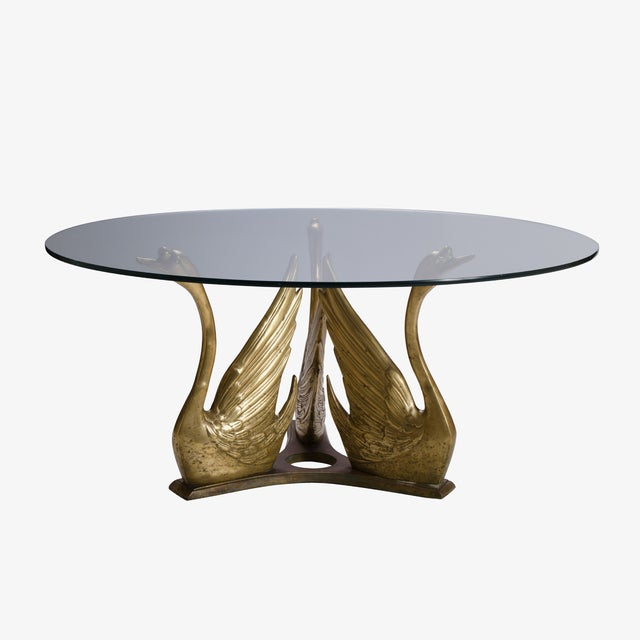 In the style of Maison Jansen, a flock of three-seat brass swans support a round piece of glass, making an elegant...