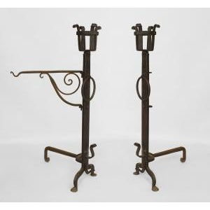 Pair of American Mission style (19/20th Cent) monumental wrought iron andirons with basket tops and a detachable swivel kettle holder