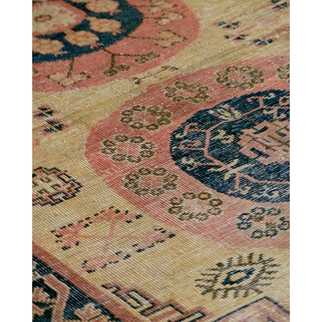 This antique Khotan rug has a golden-yellow field scattered with dusty-pink flowering plants and lozenges issuing...