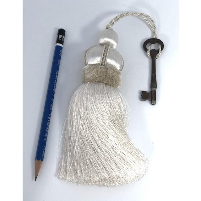 One ivory/white colored key tassel with hand cut velvet ruche, decorative gimp and twisted cord detail. Please note:...