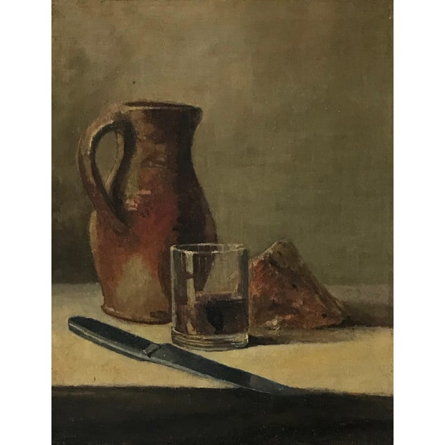 This is a lovely early 20th century still life painting depicting a wine jug and a block of cheese from France.