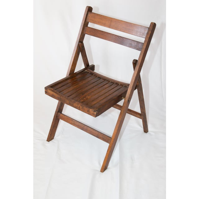 Charming mid 20th-Century wooden folding chair with a slat back and seat. This chair is sturdy and hand crafted from fine...