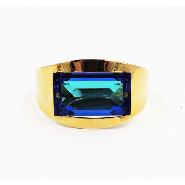 "1970s goldtone open backed rectangular blue rhinestone cuff bracelet. Marked ""Bijoux Cascio."" Opening; 6/8 inches W with..."