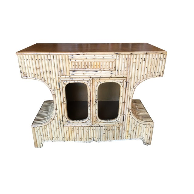 """Vertically stacked rattan """"Anvil"""" shaped sofa table cabinet with a mahogany top resting on an arched base. It contains a..."""