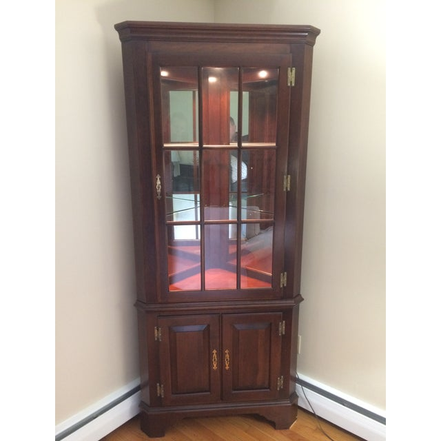Corner china cabinet with cherry finish. Bottom cabinet has double doors with a single shelf. Top door is a glass with 9...