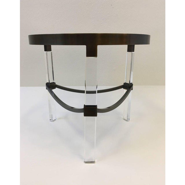 """A glamorous 1970s """"Regency"""" side table by Charles Hollis Jones. The table is constructed with bronze, acrylic and bronze..."""
