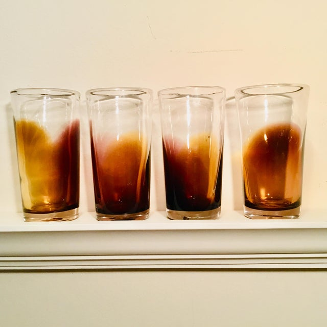 Set of 4 handblown tall drinking glasses. Each glass has its own unique golden brown ombre design.