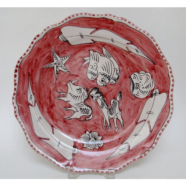 Vintage ceramic serving plate with free form hand-painted flora and fauna in black and white against soft red glaze....