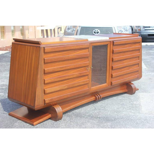 French Art Deco masterpiece buffet in solid mahogany. By famed designer Gaston Poisson. Circa 1940s. Detailed throughout,...