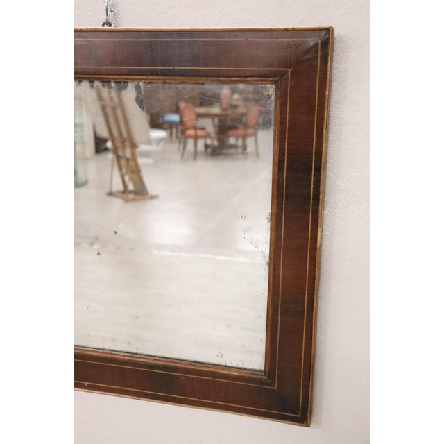 Refined wall mirror from circa 1825 in the middle of the period Charles X, made of veneered walnut with an elegant maple...