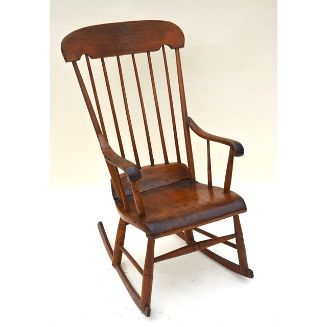 A Windsor stick-back Boston rocking chair with traditional s-shaped front lip rolling down and back lip rolling up making...