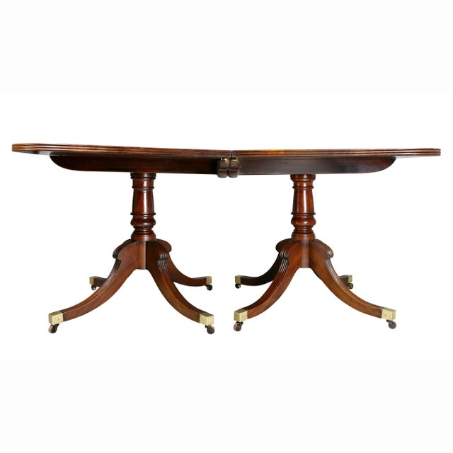 With rectangular top with rounded corners supported on two pedestal bases each with four splayed legs with cups and...