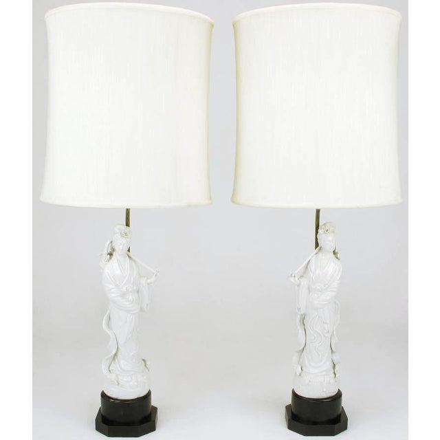 Pair of white porcelain blanc de chine table lamps. Asian statuettes of women carrying baskets of roses over their...
