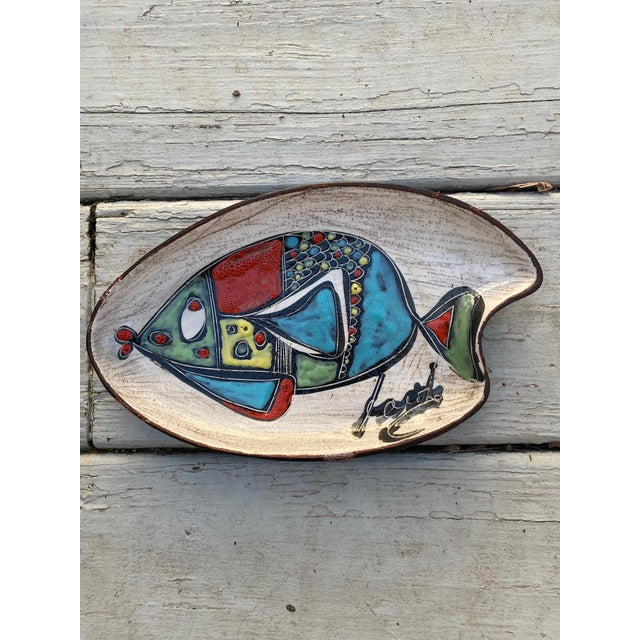 Leather wrapped ceramic shaped tray in the style of Marcello Fantoni. Featuring a colorful hand painted fish on a striated...