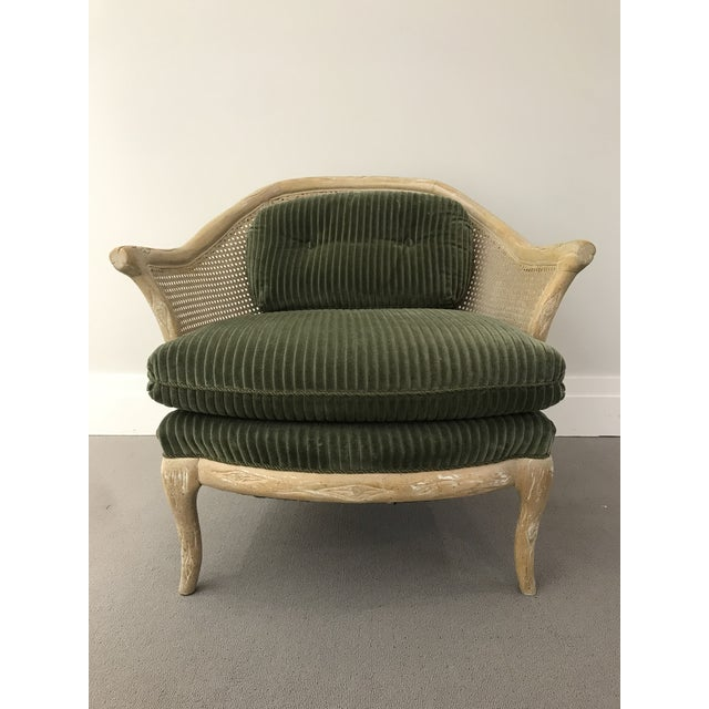 Vintage round distressed faux bois arm chair with cane back and arms. Green corduroy upholstery and corded piping on seat...