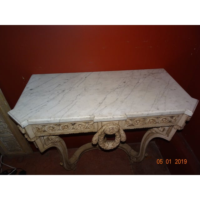Single 19th Century French carved wood console with one inch molded carrara marble top. Painted in an antique white. Apron...