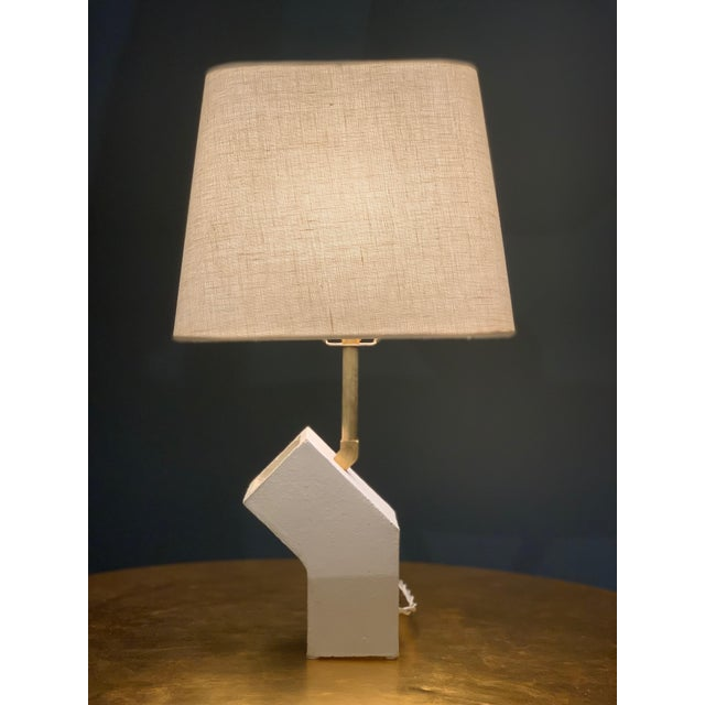 Structural ceramic lamp with brass accents and a warm white shade.