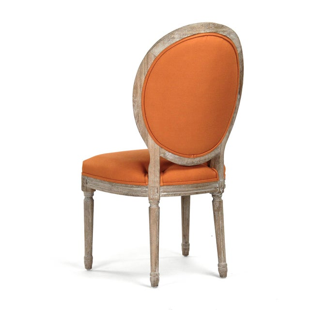 Round tufted back side chair upholstered in orange linen on limed grey oak frame.