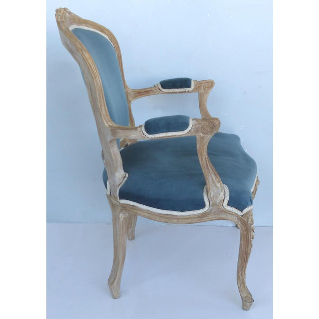 Offered for sale is an antique pair of French Louis XV style armchairs with a limed finish, upholstered seats in a Celeste...