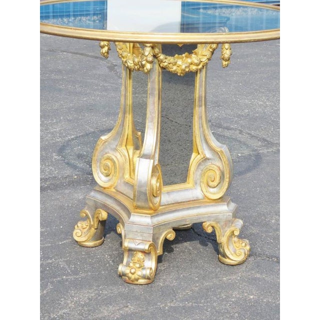 Directoire style glass top center table with gilt highlights and mirrored panels.
