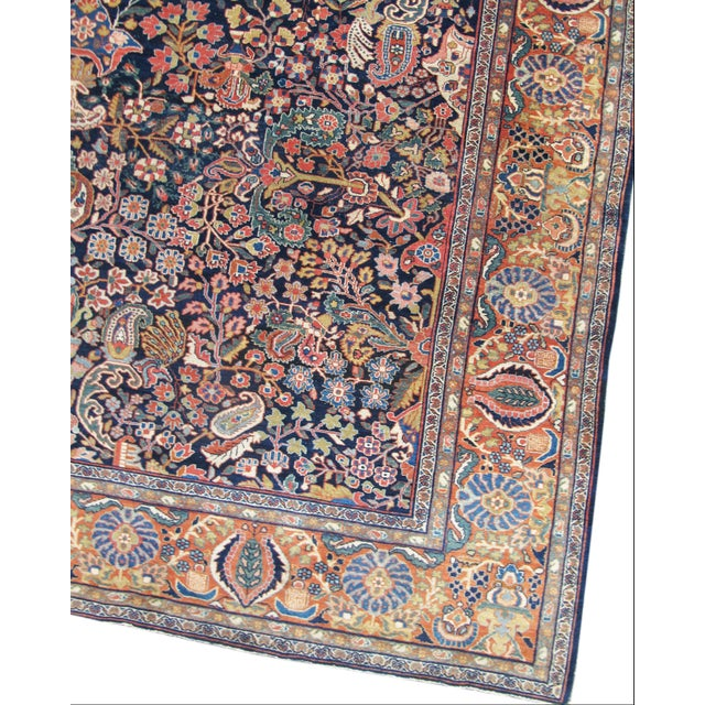 Elegantly woven with rich autumnal colors against an indigo ground, this Fereghan carpet from central Persia combines an...