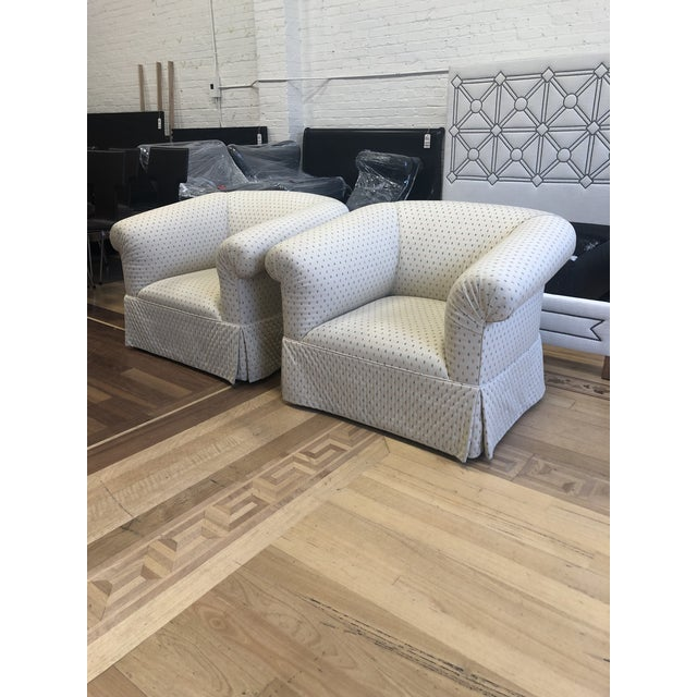 Design Plus Gallery presents a pair of swivel chairs. Custom designed with rolled arm and back. Upholstered in a ivory...