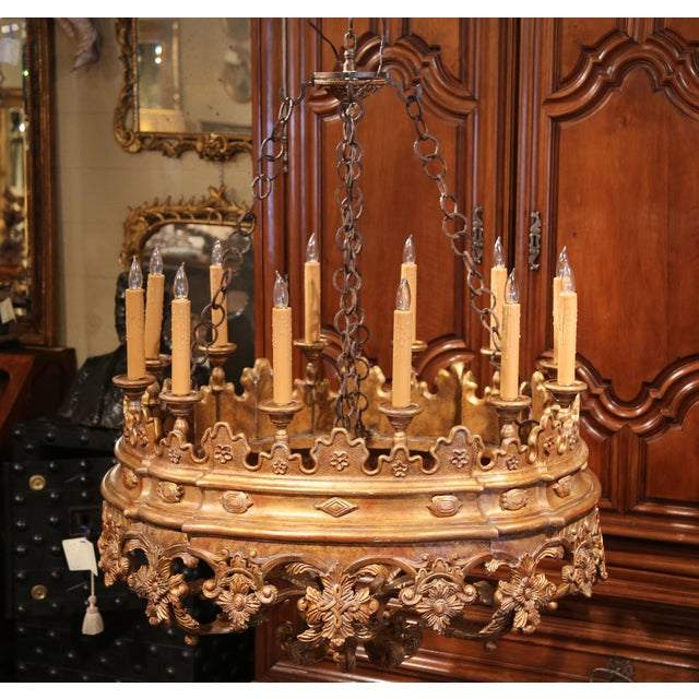 This large, carved light fixture was created in Italy circa 1980. This vintage, oblong chandelier has twelve lights and...