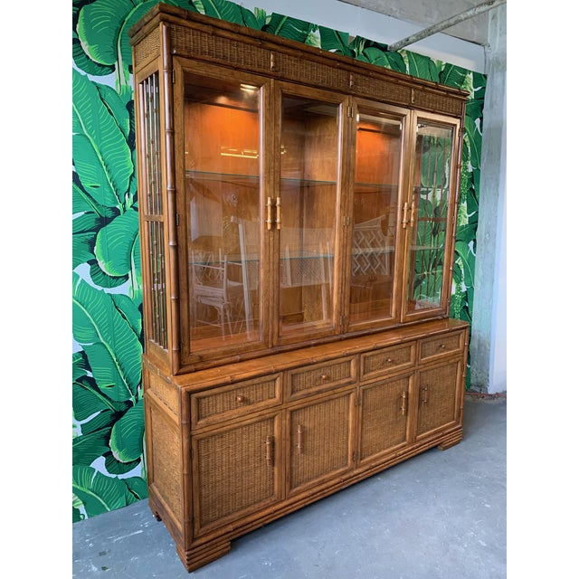 Large faux bamboo china cabinet features lighted display cabinet, glass shelving, and wicker detailing on door and drawer...