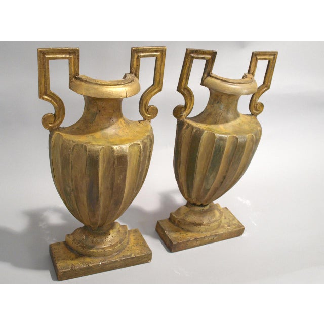 Pair of divided urns, once whole, Neoclassical period, of carved wood with distressed, painted finish; each having fluted...