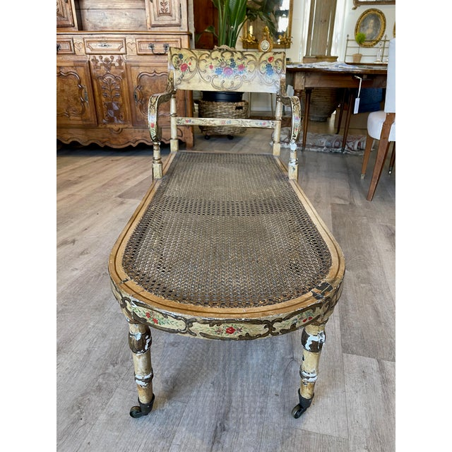 Delightful Paint decorated and caned recamier, c.1830, likely Regency, the curved tablet form crest rail atop thin...
