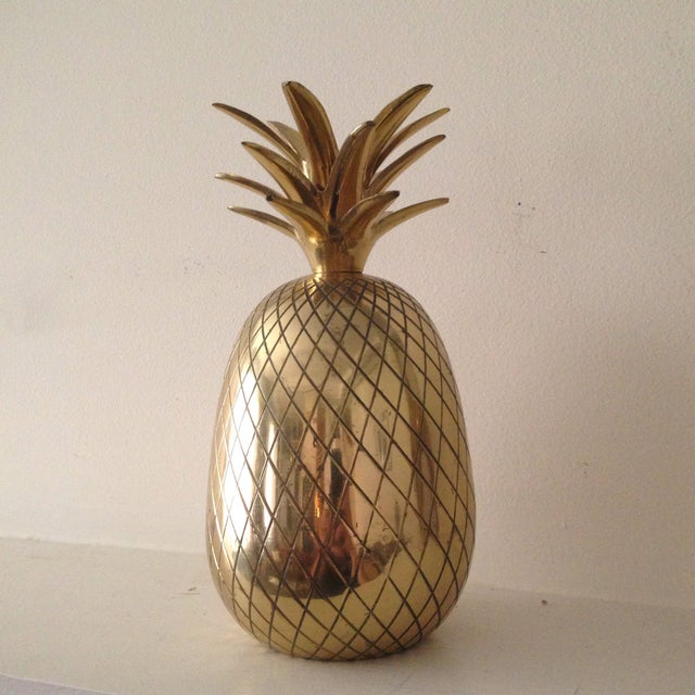 "Who doesn't love a juicy pineapple? This shiny 9"" brass pineapple candleholder is ready to glam up any space! This..."