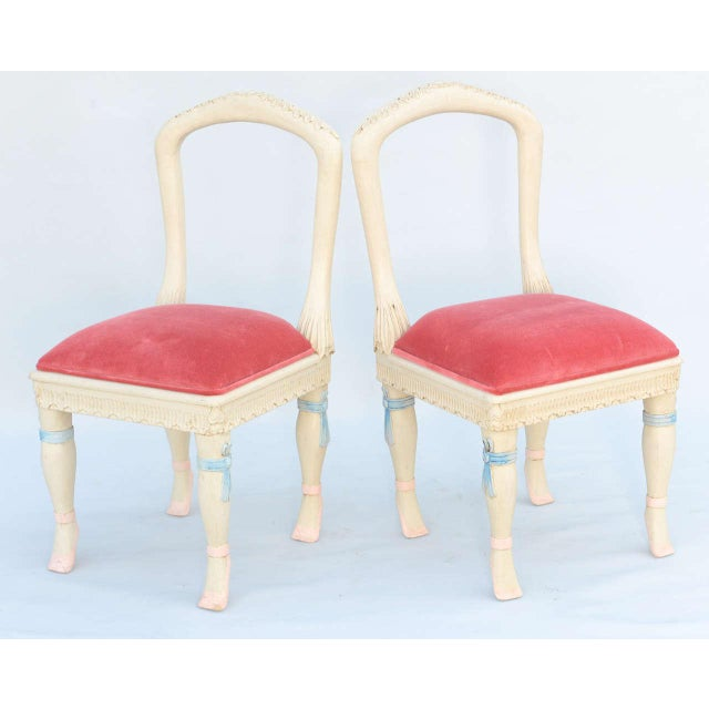 Set of four chairs, having painted finish showing natural wear, each having open arched back rests, drop-in crown seat on...