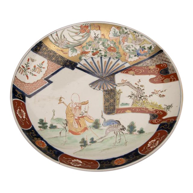 An Imari charger from Arita, Japan c. 1875 featuring a scholar reading a scroll in a landscape surrounded by three cranes For Sale