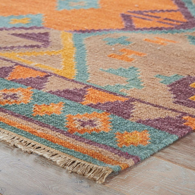 This traditional-style kilim area rug boasts a geometric diamond design in a vibrant orange, purple, and teal colorway....