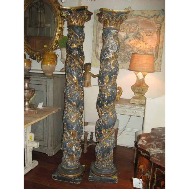 Pair of French 17th Century carved painted wood columns with gilt wood capitals. The color is a dark blue. The barley...