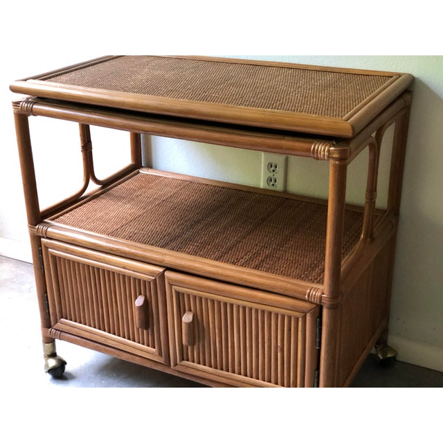 1970s bamboo bar cart with swivel top and brass details. Rubber casters with brass covers glide smoothly and there is...