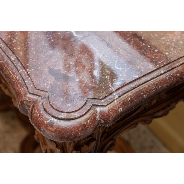Marble top console, with carved wood base with a painted finish. The marble is deep rouge with two levels of beveling and...