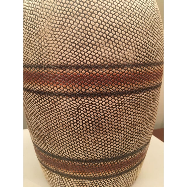 French mid-century ceramic table lamp featuring a vessel shaped turned body done in a snakeskin texture in cream over...