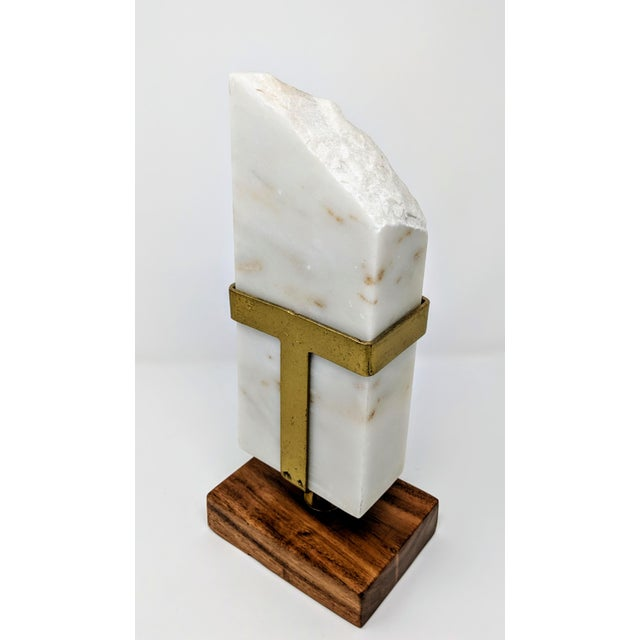 This white marble and brass sculpture is suspended on a wooden base. The white marble has beautiful caramel veining...