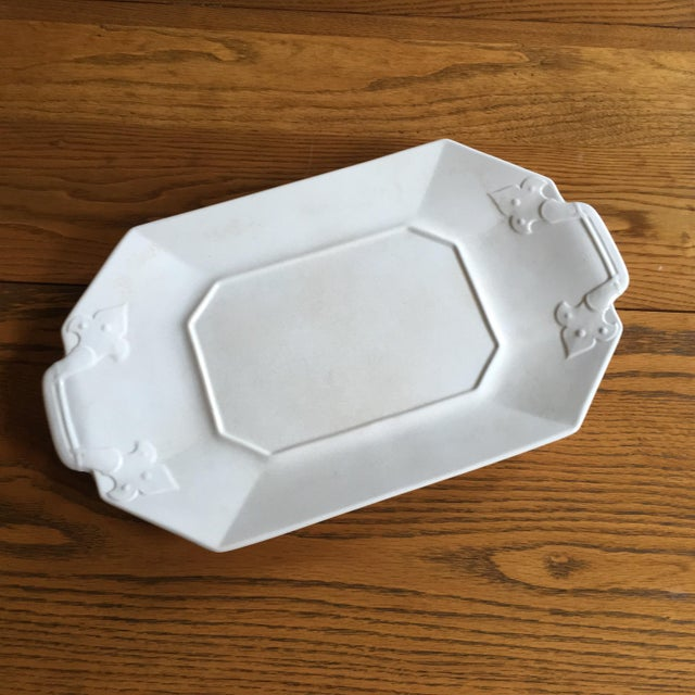 This vintage white serving tray has an antique finish with even crackling throughout and interesting handle details...