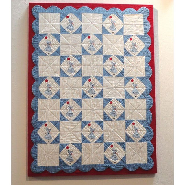 Folky and fantastic sunbonnet Sue mounted applique crib quilt. The little girl is holding a red balloon and the quilt is...