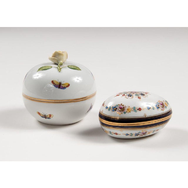 A precious set of two porcelain rounded boxes with handprinted floral design, both marked. The egg-shaped box is Meissen...