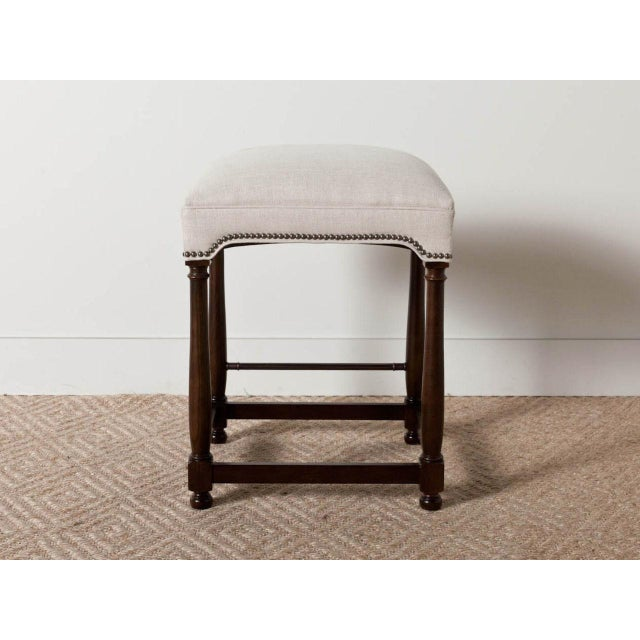 Upholstered stool with wooden baluster frame. Exposed nail head detail.